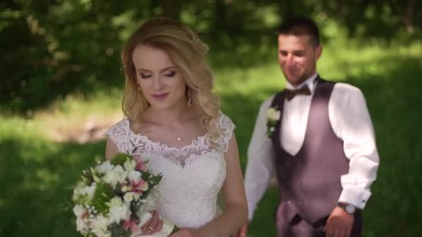 Groom comes to charming blonde bride with bouquet behind her. Slow motion