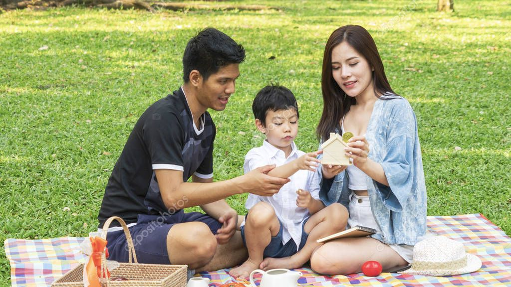 boy hold money saving house box with mother and father in park.Happy family picnic concept.