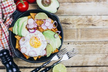 Homemade chilaquiles breakfast: nachos with tomato salsa, avocado and fried egg