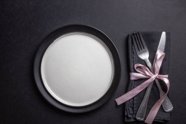 Elegant black table setting: plates, napkin and silverware over black background. Flat lay. copy space stock vector