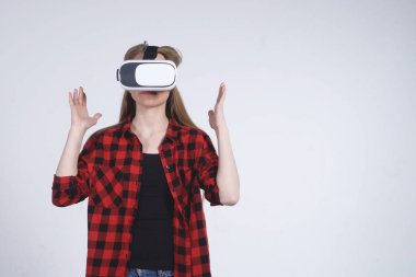 The Young Girl in the Virtual Reality Helmet is Actively Playing the Game