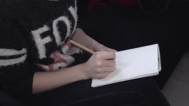 Lány felhívja egy ceruzával papírra. Rajz, vázlatok, közeli női designer