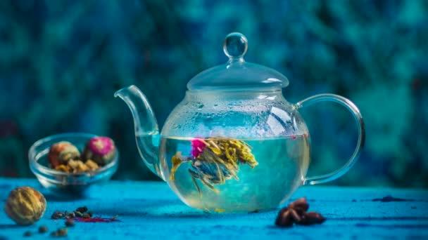 tea cerium on a blue background, tea is dissolved in a teapot, art emerald background, a flower of tea is dissolved in a teapot time-lapse.
