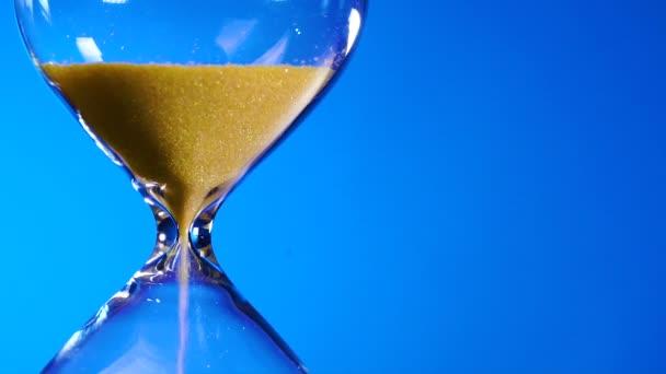 Homokóra sárga homok egy átlátszó lombikba testét, kiterítvén a kék háttér és fogytán az idő.