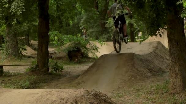 Mladý muž, jízda na kole. Cyklista v lese. Jízda na koni a skákat přes překážky. Půjčovna kol. Zpomalený pohyb