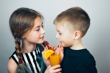 Children drink juice through straws from the same glass. Boy and girl on grey background.