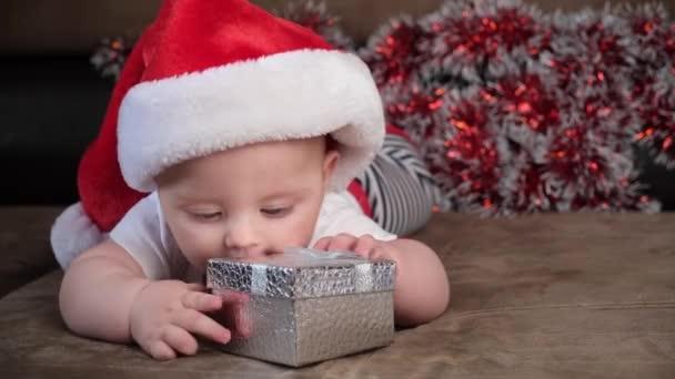 Niedlicher kleiner Junge hält Weihnachtsgeschenkbox auf Sofa liegend.