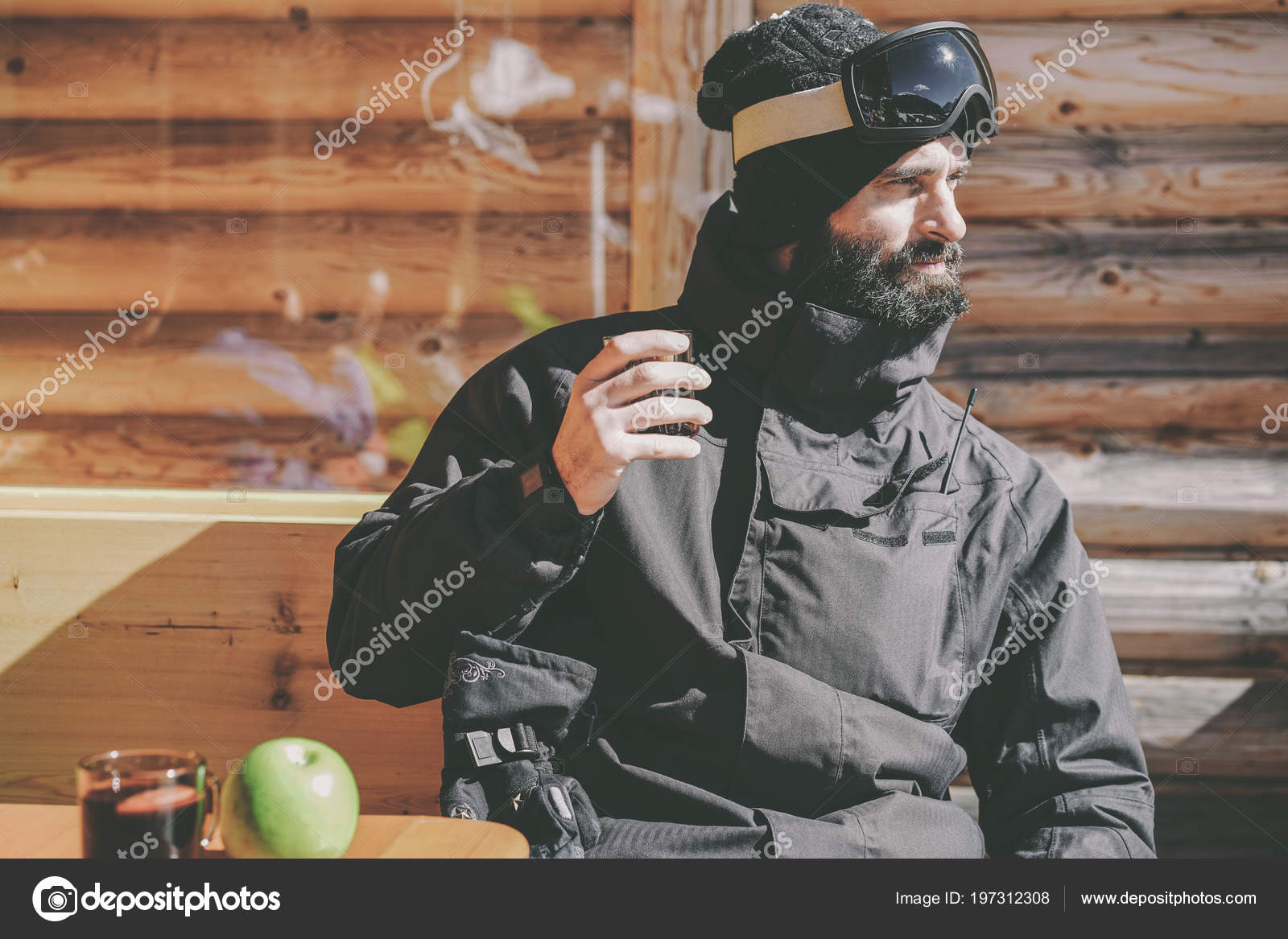 Bearded cool snowboarded taking rest after ride session