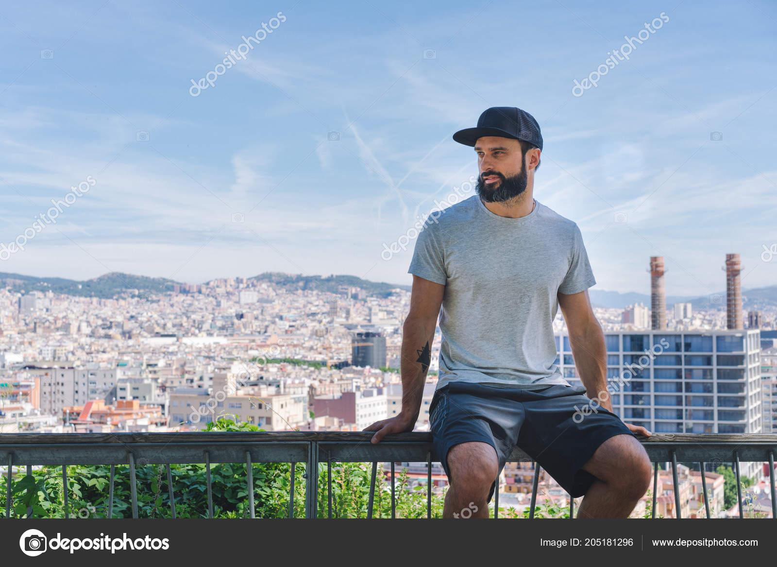 1ab6d267afbf0 Modelo de homem barbudo hipster muscular usando cinza t-shirt em branco e  um boné preto com espaço para seu logotipo ou desenho em estilo urbano  casual ...