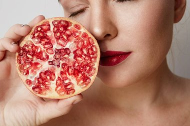 Beauty woman with orange pomegranate cut in half over white background. Attractive fresh vitamin concept. Closeup