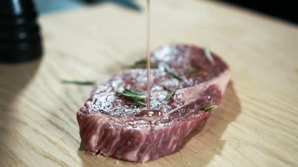 Mladý kuchař zalije hovězí steak s omáčkou v kuchyni z baru.