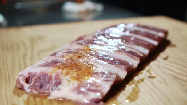 Mladý kuchař posype plátky masa s kořením v kuchyni z baru.