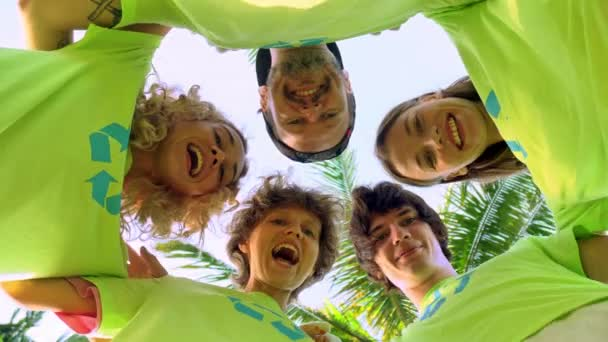 Five young volunteers in green t-shirts with a picture of recycle forming huddles under palm trees on the shore of an ocean beach, after cleaning the beach from plastic debris. Volunteering and
