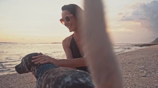 Young Carefree Woman in Sunglasses Playing with Dog, Stroke a and Kissing Dog on the Beach During Amazing Sunset. Sea Summer Vacation Concept
