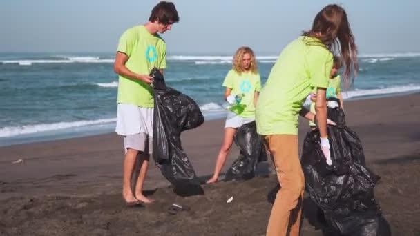 Vier Freiwillige in grünen T-shirts mit Bild Recycling sammeln Müll am Strand, vor der Kamera mit Taschen von gesammelten Müll suchen. Freiwilligenarbeit und recycling-Konzept. Umweltbewusstsein textfreiraum