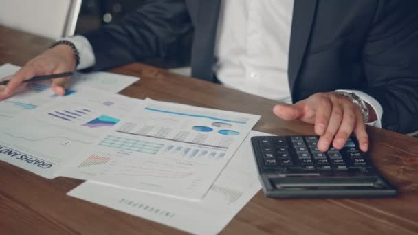Close up of a businessman hands with pen working at office desk and analyzing graphs and charts and writing a business plan. Trader man monitoring annual business report. Business concept