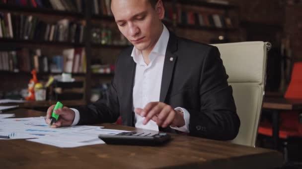Mladý podnikatel na sobě oblek, práci s dokumenty a kalkulačka sedí v kanceláři, finanční analytik, použití nebo ekonom peněženek. Podnikání, lidé, papírování koncepce