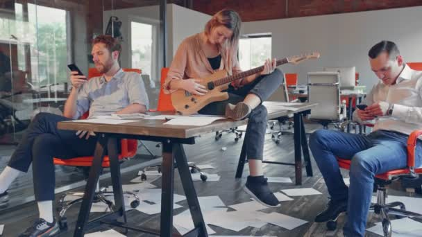 Upset business group of young people are bored in the office without work after a failure of business meeting. A woman with guitar setting on a table, two mens are playing with a phones. the paper is