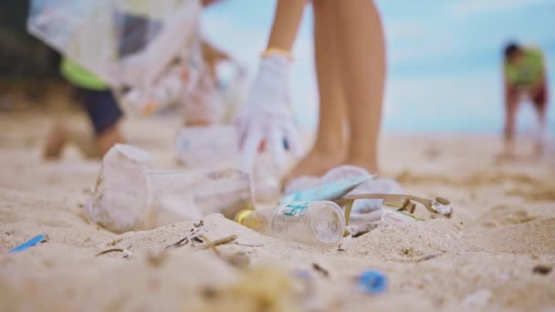 Group of volunteers cleaning up beach. The volunteer raises and throws a plastic garbage into the bag. Volunteering and recycling concept. Environmental awareness concept copy space