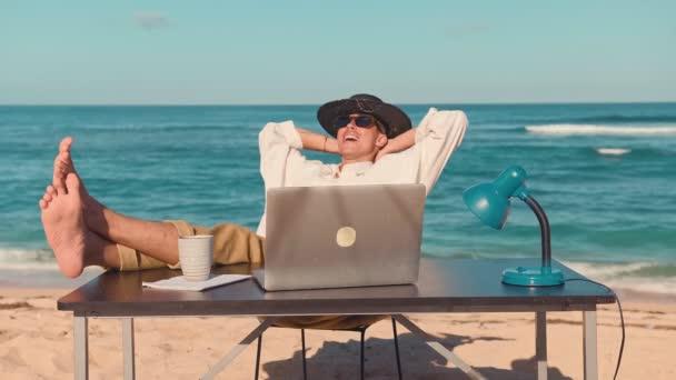 Egy fiatal férfi ül a strandon laptop, pihenő üzembe lábát az asztalra