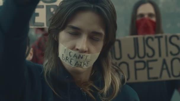 Skupinoví demonstranti s páskou na ústech držící kartonový štítek se slogany