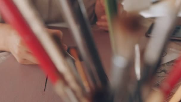 Nahaufnahme Hand der Künstlerin hält einen Pinsel, zeichnen Sie einen Satelliten der Erde mit Öl