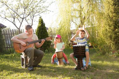 Happy family dad and two kids having fun with musical instruments together outdoors. Dad playing guitar and kids playing ethnic drums. quarantine. musical concept