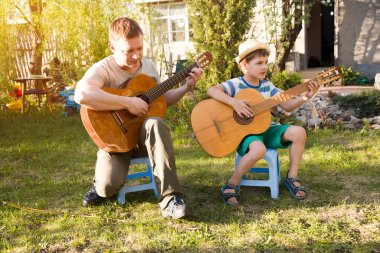 Happy family dad and child son having fun with musical instruments guitars together outdoors. Dad teaches son how to play guitar. quarantine. musical concept