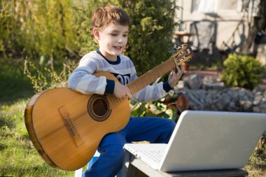 Kid boy playing guitar and watching online lessons on laptop while practicing outdoors. quarantine.