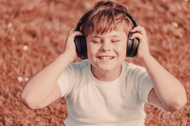 boy with headphones listening to music while sitting on the grass