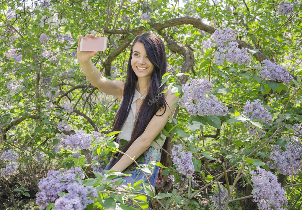 girl with long hair takes a photo on the phone while sitting on a branch of a blossoming lilac tree