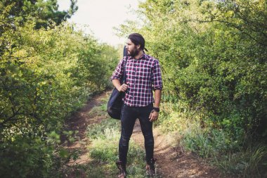 Young bearded male with long hair and guitar, portrait of traveler musician hiking in the forest
