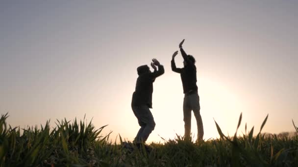silhouette of two young peoples running, jumping and having fun in spring fields, sunset background