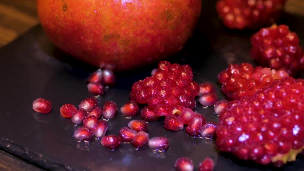 Fresh colorful pomegranates fruits close up on black table