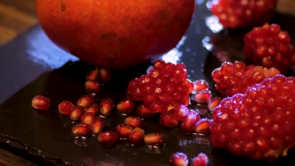 Svěží barevné granátová jablka ovoce zblízka na černý stůl