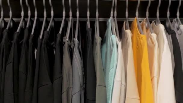 Velké množství triček na věšáku v obchodě
