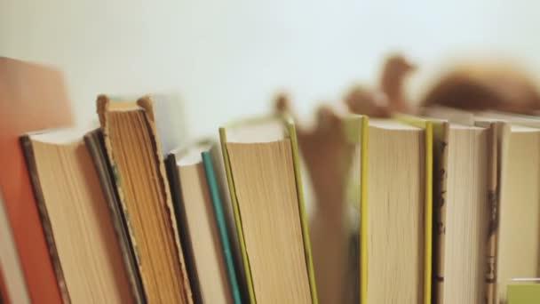 mladá žena vybrat knihy na polici