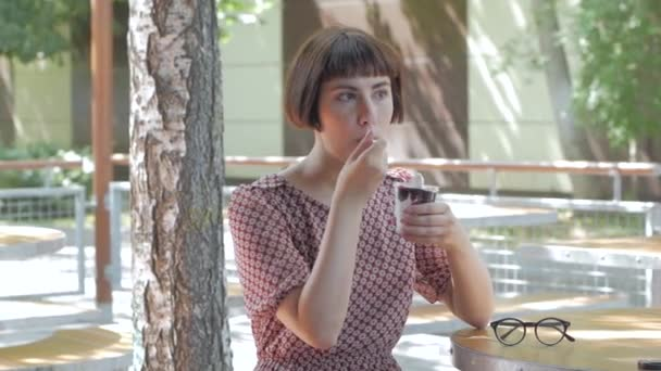 Young woman eat ice cream outdoors