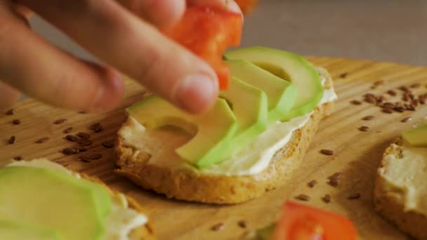 Fresh toasts with avocado and tomatoes on wooden table