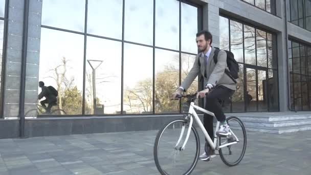 Modern young businessman bicycle rider in suit and with backpack outdoors
