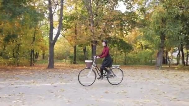 mladá žena na koni na retro kolo v podzimním parku