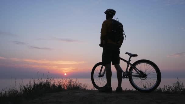 Mužská jízda na horském kole v blízkosti moře proti krásnému západu slunce
