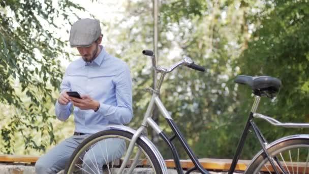 Mladý stylový muž s retro jízdou na kole na ulicích ve slunečný den, portrét moderního obchodníka s mobilním telefonem