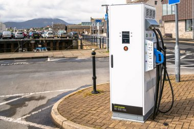 Photo of a charging point for electric vehicles along a harbourside road in a coastal town on a sunny summer day. Stromness, Orkney Islands, Scotland, UK.