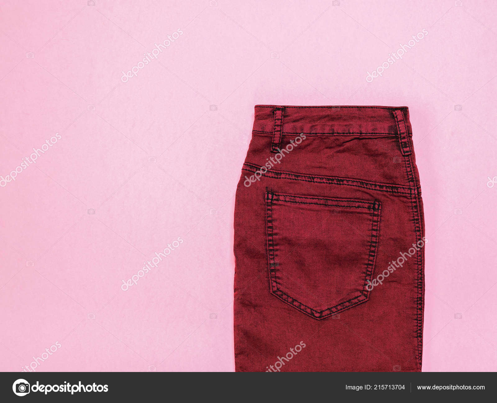 51b665673 Burgundy denim skirt on pink background. Fashionable denim women's  clothing. Denim women's clothing on colored background.