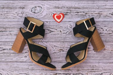 Fashionable suede women's shoes and a heart on a wooden background. Flat lay.
