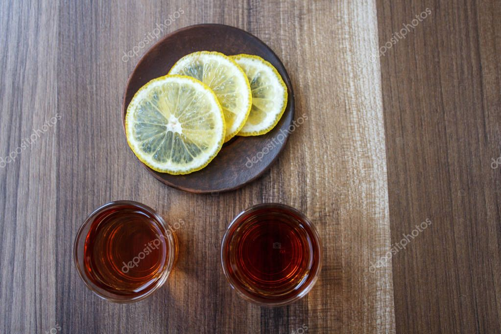 a two piles of whiskey and slices of lemon on a wooden background