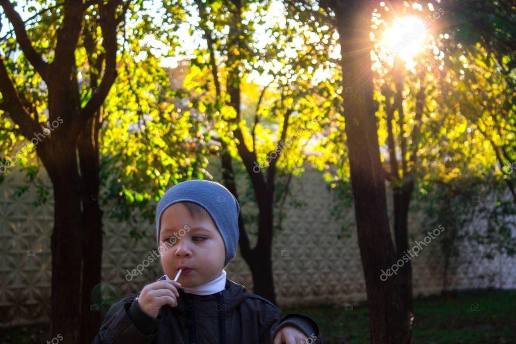 little boy licking a lollipop in the street