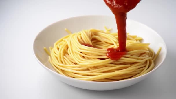 Delicious vegan tomato sauce beeing poured in a plate with spaghetti. Slow motion. White background. Camera movement from right to left