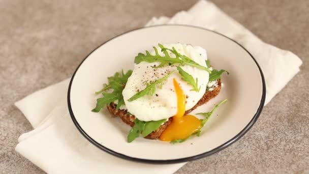 Rye bread toast with poached egg, dairy cream, spices and arugula. Continental breakfast. Healthy food concept. Horizontal view